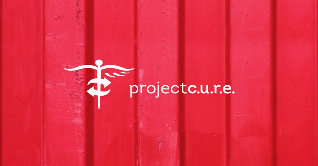 """Project C.U.R.E. logo shows a caduceus with global arrows and the words """"Project C.U.R.E."""" as part of logo"""