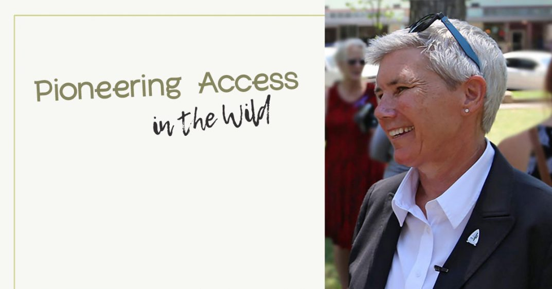 Text: Pioneering Access in the wild. To the right is a portrait of Sue Black. She is a woman smiling in profile. She has short silver hair and wears blue sunglasses on top of her head. She is dressed in a suit.