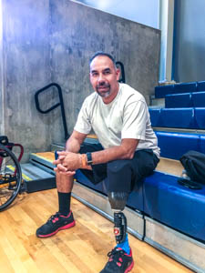 Richard Alcaraz smiles at the camera. He sits on bleachers, hands folded on his knees. His front leg is a prosthetic device.