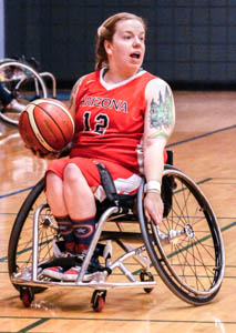 Sarah Heinzel is shown playing wheelchair basketball. She wears a U of A Arizona number 12 jersey. She has a tattoo on her upper arm.