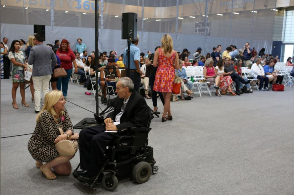 Phil Pangrazio speaking with a woman at an event.