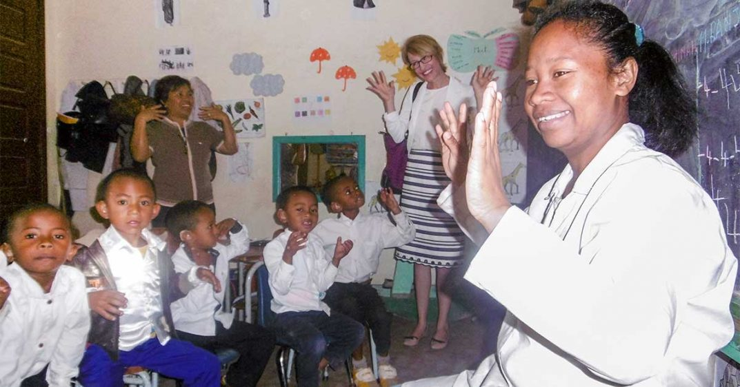 Photo shows April Reid with children from Madagascar in a classroom. They are making the ASL symbol for applause.
