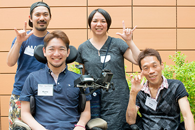 "Photo shows four members of the Japanese delegation, one in a wheelchair with a sophisticated joystick. All smile at the camera. They make the ASL universal symbol for ""I love you."""
