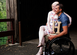 A young couple who appears to be in a barn looking out on this setting sit together. He is a wheelchair user, manual wheelchair. He wears brown cargo pants and a blue shirt. She is a very fair-skinned woman in a dress sitting on his lap. Her dress is floral. Her legs are crossed. She wears sandals. She holds a very large wooden H.