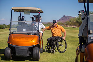 Photo shows a golf fairway with mountains in the background and a golf cart. On the front of the golf cart is the Longbow Golf Club logo. Two sets of golf clubs are loaded in behind. A man sits in the driver's seat and looks at his companion, a man using a manual wheelchair wearing an orange golf shirt. They smile at each other in conversation.