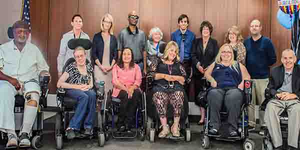 portrait of all of the graduates of the Community Leadership Academy class. Five of them sit in wheelchairs. Phil Pangrazio, Amina Kruck, and April Reed join them. The group smiles at the camera.