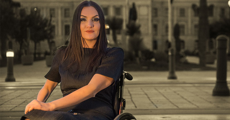 Photo shows a young woman in a black dress and long, dark hair. She sits in a wheelchair in front of the Arizona State Capitol.