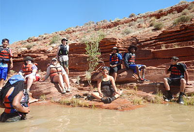 A group of individuals sit on the red rocks next to the Colorado River.