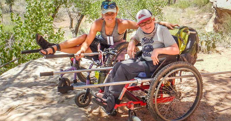 Brenna Bean sits next to a young man in a safari chair. This is a wheelchair with long, long poles so someone can pull the chair like a rickshaw.