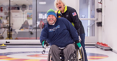 Tim Surry sits in a wheelchair wearing a stocking hat and a Ability 360 sweatshirt. He's pushing a curling stone. Holding his chair is Tracy Heuermann. They both are excited for the shot.