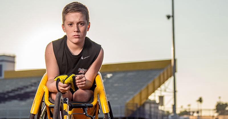 Photo is a stadium with a track, and on the track is a bright yellow racing wheelchair with a Batman logo on the front spoke. Sitting in it is a boy of maybe 10 or 12 years old with a very intense look on his face. He wears a racing helmet. It looks like a skull.