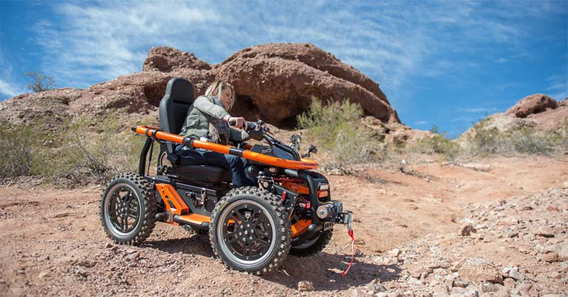 Photo shows a view of desert terrain, big rocks in the background, and scrub against a big blue sky. In the foreground is a young woman on the Terrain Hopper, a wheelchair accessible all-terrain vehicle designed specifically for wheelchair users to enjoy desert surroundings.