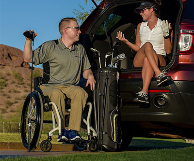 A man who uses a manual wheelchair next to a woman sitting on the edge of a van trunk. They are smiling at each other. He has a golf club in hand and they have a case in between them with golf clubs inside.