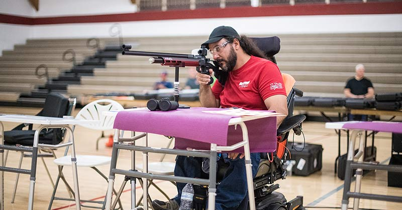 Photo shows an indoor gym. Bleachers can be seen in the background. In the foreground, a man sights a long, thin rifle. He wears a baseball cap, safety glasses, and a red t-shirt. He sits in a large power wheelchair. In front of him is a table with a pair of binoculars.
