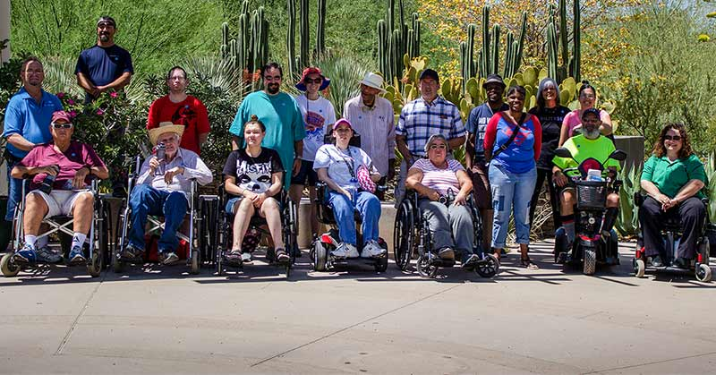 A large panoramic shot of the individuals who came out for the Socialization Through Recreation class. There are one, two, three ... six people in wheelchairs. Arrayed around them are another group of ... 12. They all smile at the camera with various desert cactus and plants in the background.