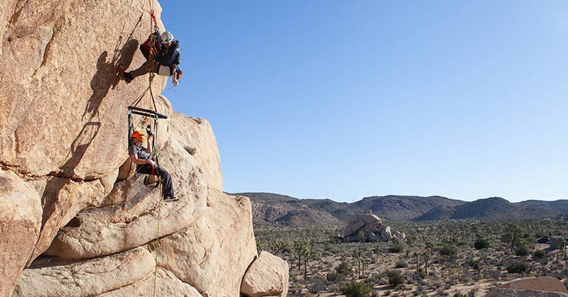 Photo shows someone suspended on a rock wall in this nylon chair with straps, webbing straps, and rock climbing ropes. They wear a helmet.