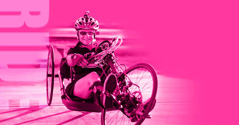 Kelly McCall sits on a recumbent bike, wears a helmet, looks at the camera. The image is pink.