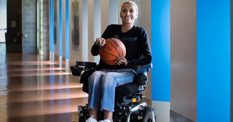 Photo shows Rola, R-O-L-A, last name A-L-L-E-W-A-W-E-H. She's blonde, her hair is pulled back. She sits in a large power wheelchair, holding a basketball and wears Ability360 branded sports gear and white tennis shoes.