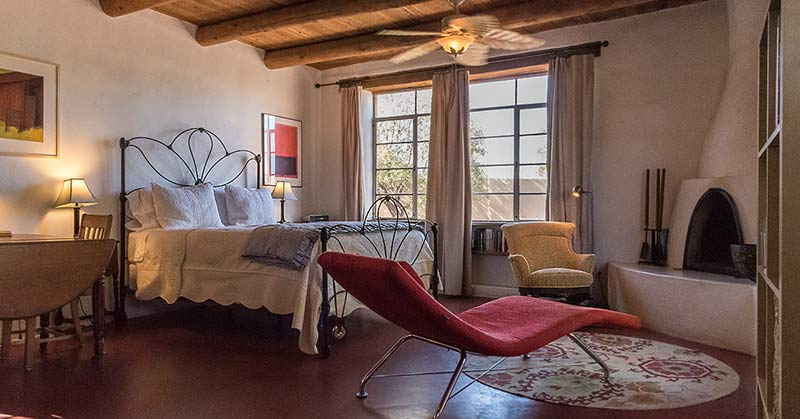 Tuscon poet studio. An open concept room with a beehive fireplace, cozy armchair, lovely red chaise lounge in the foreground, beamed ceilings, wrought iron bed frame, gorgeous tall windows framed with an inviting outdoor view and a table.