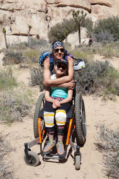 A woman hugs a young girl from behind. The young girl is using an adaptive manual wheelchair made for outdoor use. They are out in the desert.
