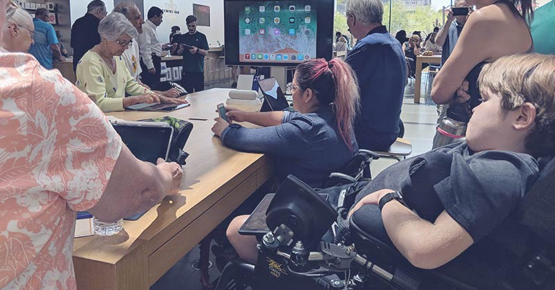 Photo shows the interior of an Apple store, a long open table in the foreground, various people around that table with tablets and cell phones, a large screen monitor in the background. In the foreground is a young man in a power wheelchair and a woman with a bright red ponytail, also using a wheelchair. She holds a cell phone at the table. The Apple emblem is obvious in the background.