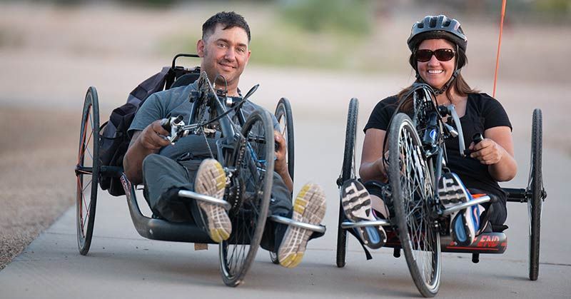 Photo of a man and a woman in recumbent bikes. She is wearing sunglasses. He is not. She wears a helmet. He does not. She has a large red flag coming up from her, the back of her bicycle.