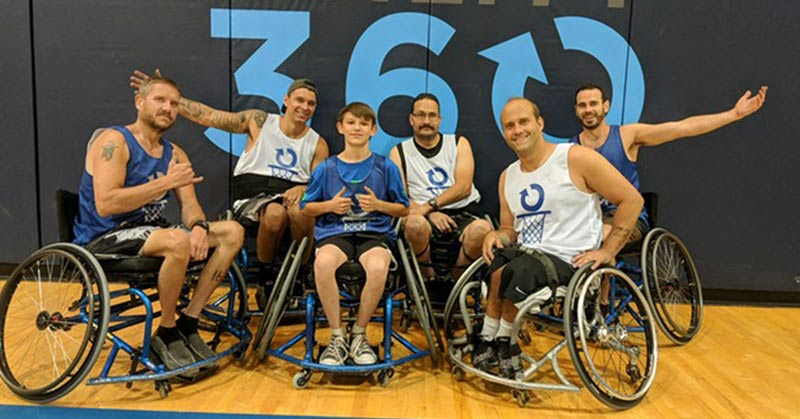 Photo. Several men on the basketball court in wheelchairs. They're wearing basketball uniforms, shorts and tank tops, the Ability360 logo behind them.
