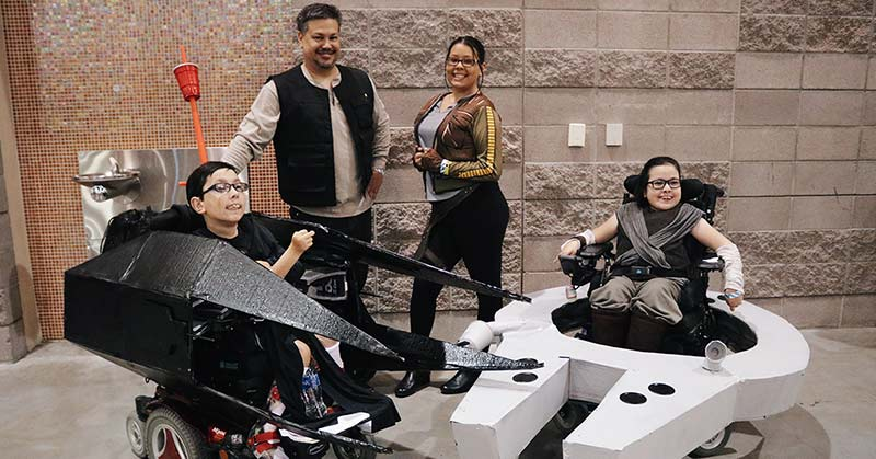 Photo shows a family together near a rock wall at the Phoenix Convention Center. In the foreground are twins Kyle and Lauren dressed as Star Wars characters. Kyle's wheelchair is wrapped with pieces that look like a Star Wars fighter, black sleek silencer. Lauren also in her wheelchair dressed as a Star Wars character has the low white TIE Fighter type ... built around her chair. In the background, a man and younger woman stand, also dressed as Star Wars characters.