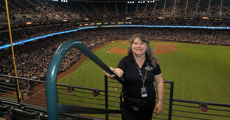 Photo shows Arizona Diamondbacks infield in the background and standing in the stadium, holding onto the handrail is Nanette, N-A-N-E-T-T-E, Odell, O-D-E-L-L.