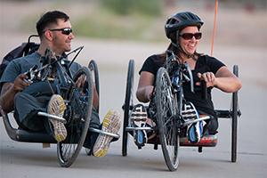 Photo of a man and a woman in recumbent bikes. They both wear sunglasses. He looks at her, smiling. She looks away, laughing. She wears a helmet. He does not. She has a large red flag coming up from her, the back of her bicycle.