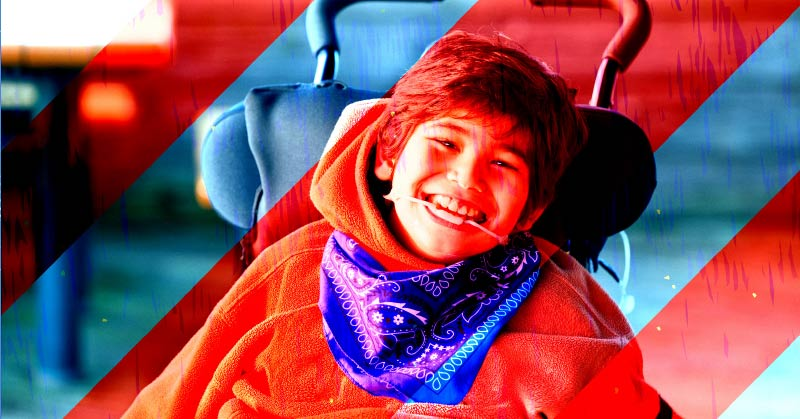 A young girl looks right at the camera and has a huge smile. She has short, dark hair. She is wearing a hoodie and blue bandana around her neck. Red and blue stripes run diagonally across the photo.