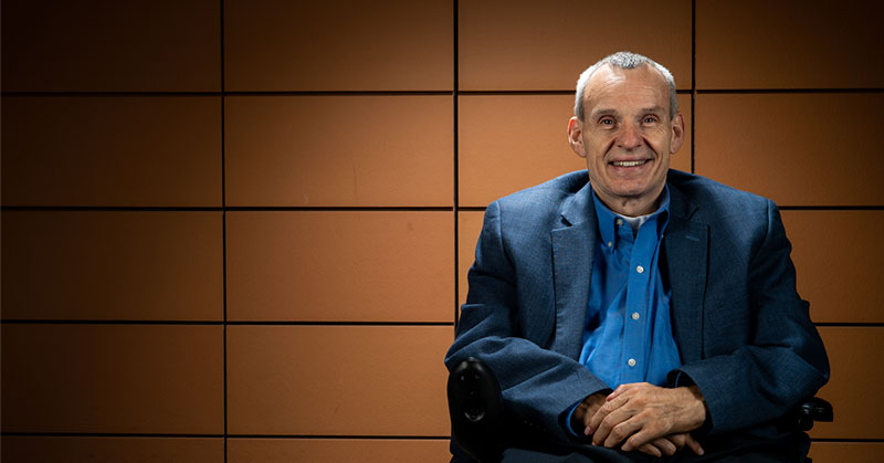 Phil sits in his chair wearing a navy blue suit coat and light blue button-up shirt. The top button of his shirt is undone. There is a terracotta tile backdrop. The lighting is focused on Phil and fades to black around him.