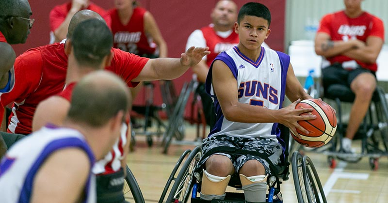 A teenage boy with olive skin and short black hair is holding an orange and off-white basketball. He is wearing a purple and white Phoenix Suns jersey and black and grey camo shorts. He is in the middle of playing wheelchair basketball. His eyes mid shut and his lips are pursed. His is clearly concentrating on his objective.