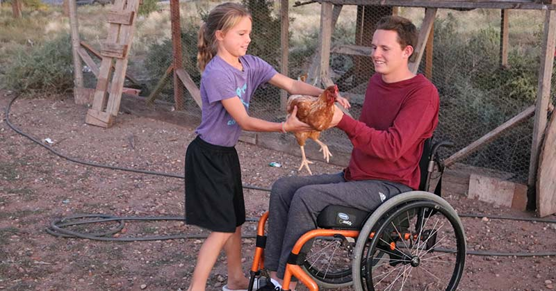 The young man in the red shirt with a younger sister who is wearing a purple t-shirt, black shorts and sandals. She is handing a red hen to her brother. He has one hand on the right wheel of his chair and his left hand is supporting the chest of the hen.