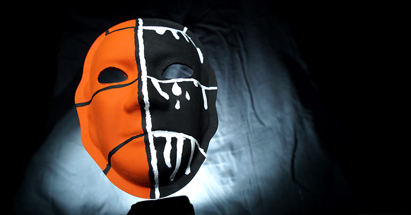 A mask divided into two colors running down the middle of the face. The left side of the face is orange with three black stripes running across the face, mimicking a basketball pattern. One is at the forehead, one is just under the eye and the last line runs just below the mouth. The right side of the face is painted black, and those same lines turn white as they cross into the right side of the face. White tear drops drip under the right eye and the strip at the mouth has three new stripes which run down towards the chin.