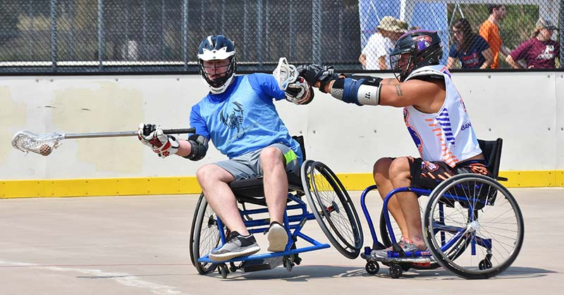 Two men are playing wheelchair lacrosse. One man is in a blue uniform and is wearing a blue and white helmet. His right arm is stretched out. He has the lacrosse ball and is headed for the goal. The second man is wearing a white and purple jersey with a helmet to match. He has both arms outstretched and is pushing the player from the other team. The man in the blue jersey is on one wheel from the push of the other player. His mouth is open and nostrils flared. He looks as though he is worried about dropping the ball. His eyes look at the ball as if to make sure he is still in possession of it.