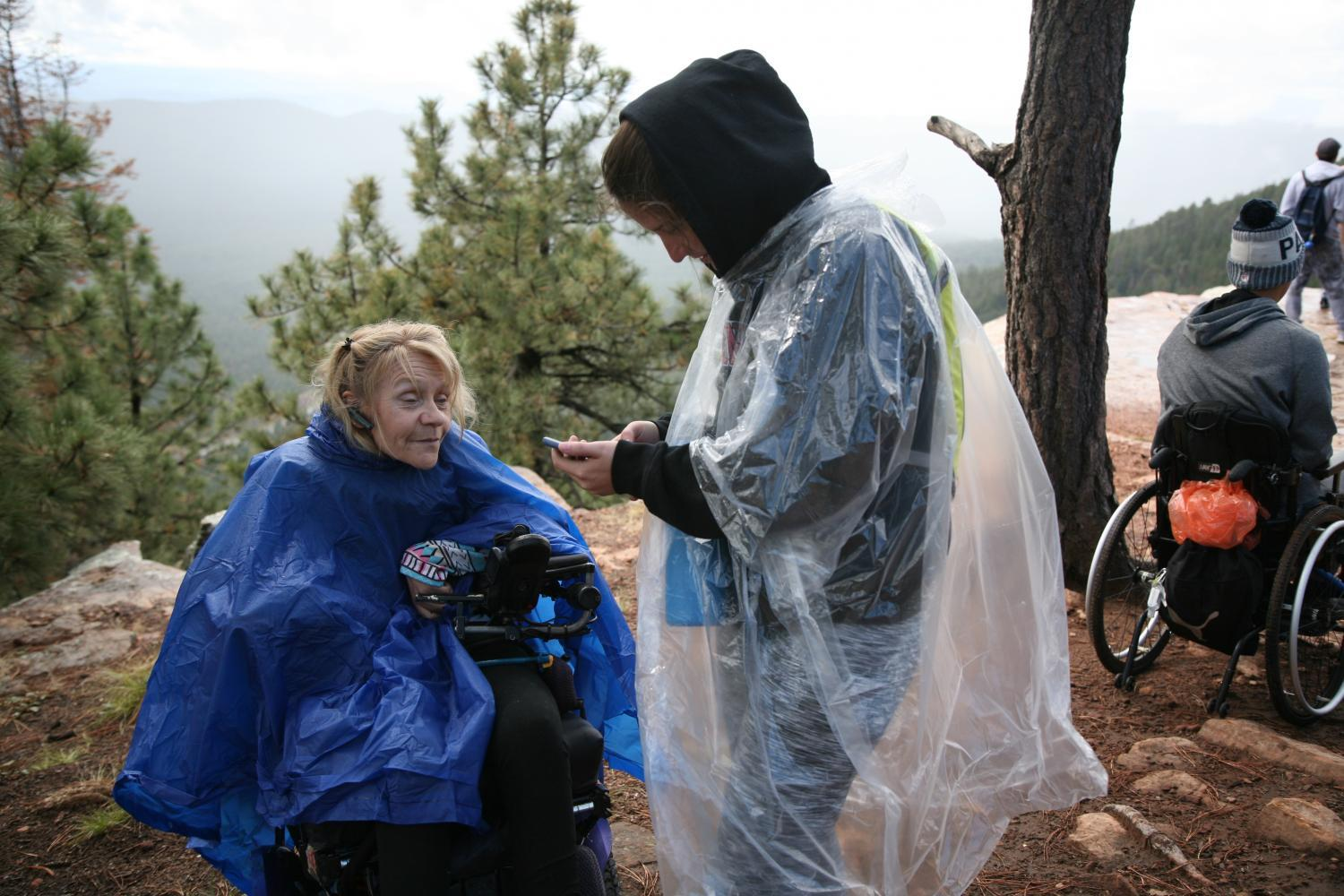 A woman who uses a power chair is outside on the edge of a cliff with another person. They both are using ponchos to protect from rain. There are pine trees and mountains in the background.