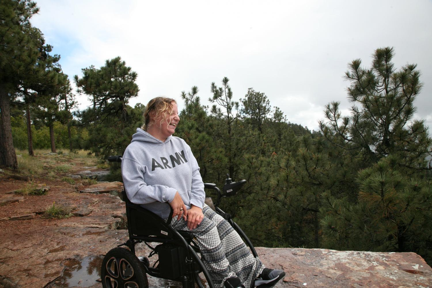 A woman who uses a manual wheelchair is outside near the edge of a cliff. There are many pine trees in the background. She smiles as she looks at the view.