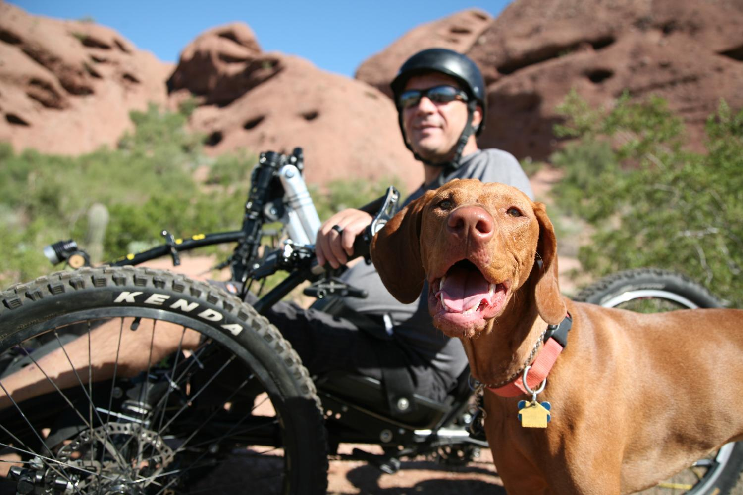 A Man outsite near Arizona mountains with his dog. He is wearing a helmet and using an adaptive hand cycle.