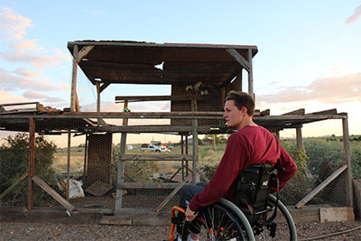 A young man in a wheelchair looks to the side. In the background is a two story homemade pen he and his siblings built for the chickens they raise.