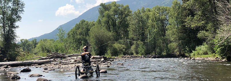 Jake O'Connor flyfishing in Colorado. Jake sits in one of his custom-made handcycles in the shallows of a river. He is wearing a tan hat and a brown shirt. Behind him are many rows of trees.