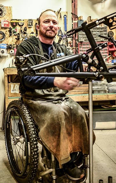 Jake O'Connor sits in his wheelchair wearing a black sweater and a dark leather welder's smock over his chest and arms. Jake smiles at the camera and works with his frame jig in his custom garage.