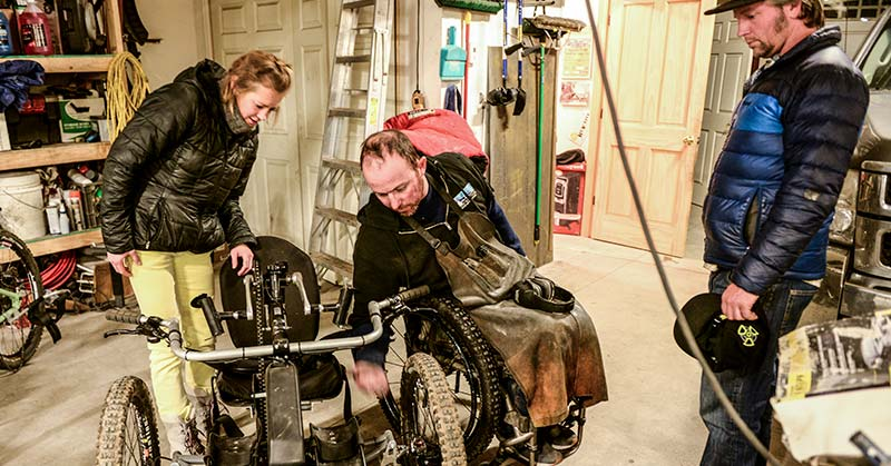 The photo shows Jake O'Connor in his manual wheelchair wearing a black sweatshirt and a dark leather welder's smock over his chest and legs. Jake is reaching towards an off-road handcycle and showing a blonde-haired woman in a black puffy jacket and bright yellow pants. On the right-hand side, another man stands looking at the woman and Jake. The man wears a black hat, a black and dark blue puffy jacket and jeans.