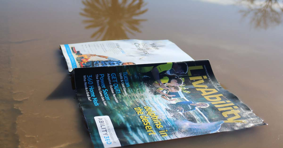 A LivAbility magazine lies face down in a murky puddle in Tempe, Arizona.