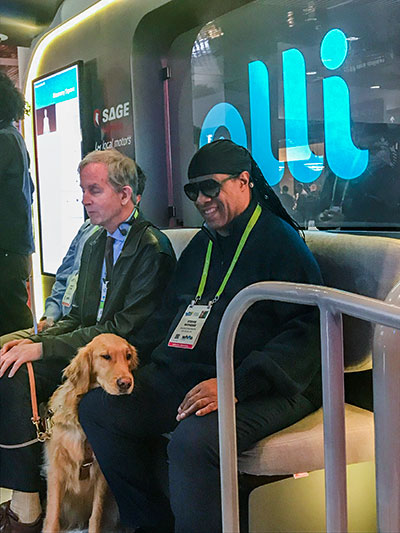 Stevie Wonder sits on the Accessible Olli. Wonder is wearing large dark sunglasses, a black pullover and black jeans. The image also shows his service animal, a fully-grown Labrador Retriever resting head on Wonder's right knee.