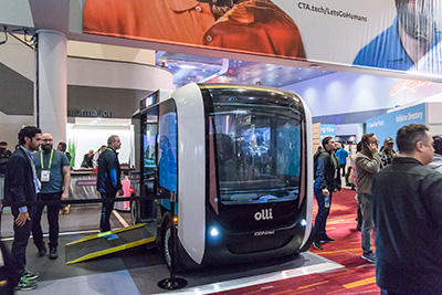 The Accessible Olli at a convention in Las Vegas. The Accessible Olli sits with the ramp out.