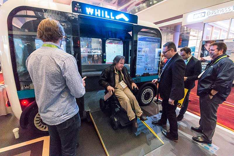 A visitor in a power wheelchair tries out the Accessible Olli prototype by Local Motors at their booth during the 2018 CES expo in Las Vegas.