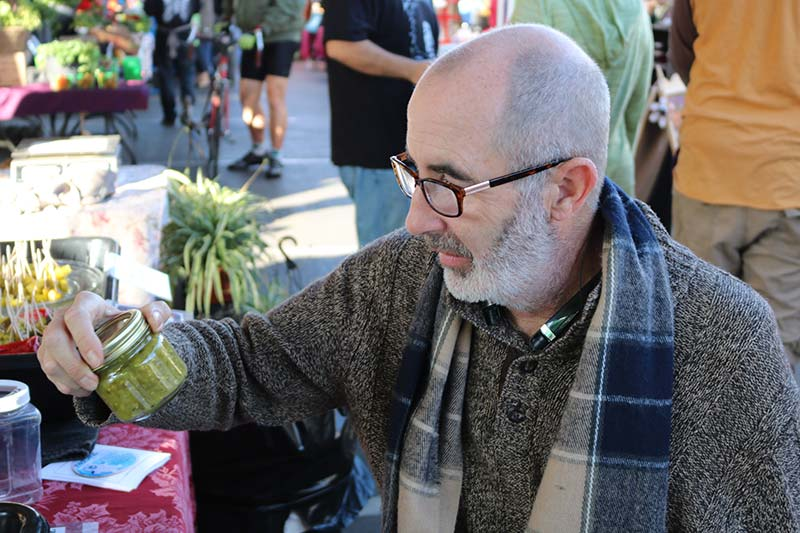 Steve Norton wears a dark grey sweater and a brown and black scarf to combat the chilly air. Norton is sporting a full gray beard, dark glasses, and holds up a jar to inspect the contents.