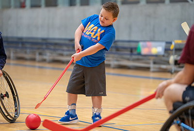 A young boy playing wheelchair hockey. The boy is standing, wearing a bright blue Max in Motion shirt, black basketball shorts, and black Nike's playing with a red hockey stick.