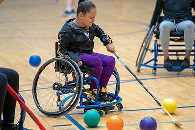 A young girl in a blue manual wheelchair playing wheelchair hockey. The young girl wears a black jacket, and blue pants with red polka dots.